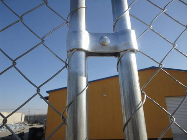 A close up picture of galvanized clamp installed to connect the two temporary chain link fence panels.